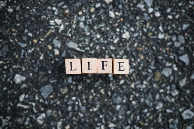 何のために生きるのかをイメージしたLIFEと書かれたブロックの置かれたコンクリの画像