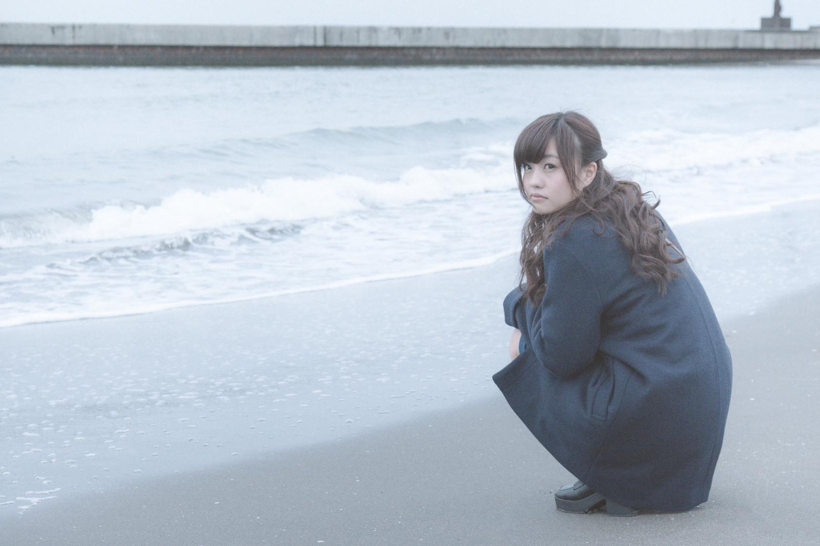 人生なんとかなると言いながら浜辺に座り込んでいる女性の画像