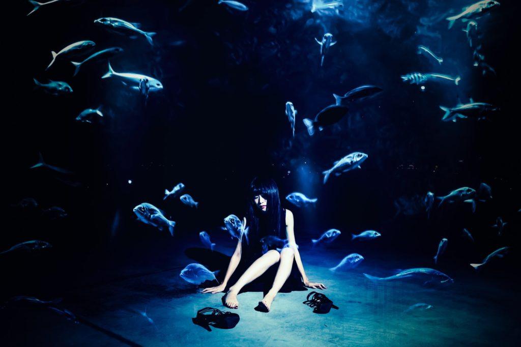 魚の大群の中に落ち込んで座り込んでいる女性の画像
