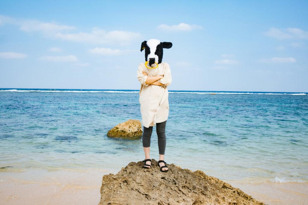 牛の被り物をしている女性が岩場の上に仁王立ちしている画像