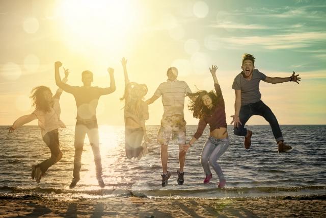 海辺で5人の男女がジャンプしている画像
