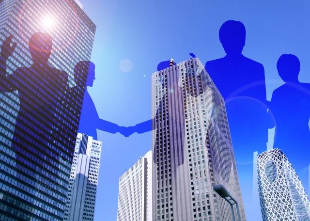 フリーランスで生きることを決めた人たちのシルエットと都会のビルの画像