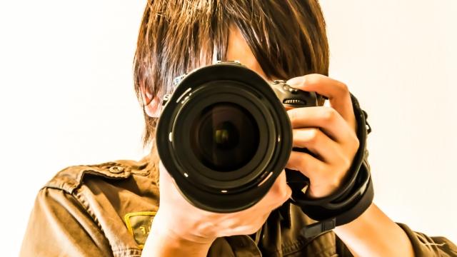 一眼レフカメラでこちらを撮っている男性の画像
