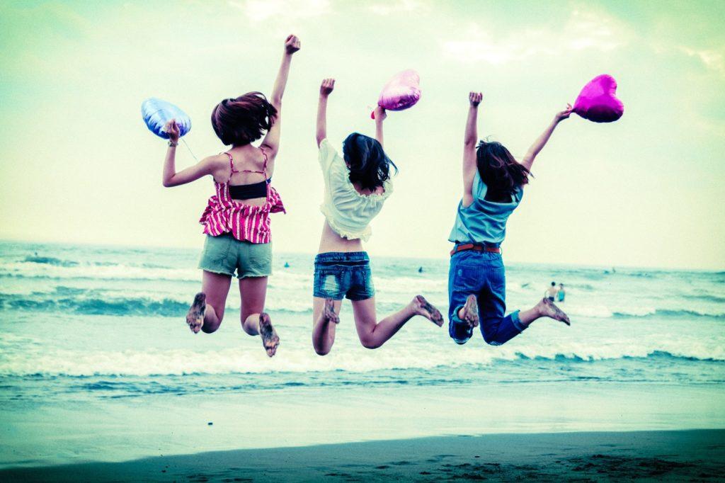 海辺で3人の女性がジャンプしている画像