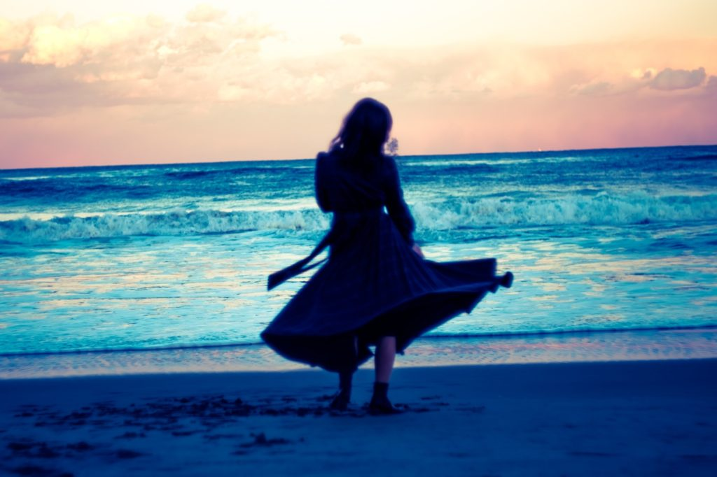 夕暮れの浜辺で立っているスカート姿の女性の後ろ姿の画像
