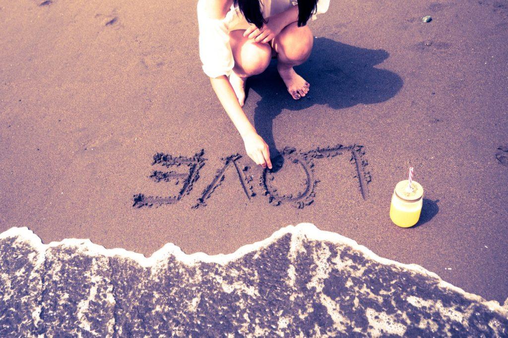 助けてほしいが言えずに一人で海で黄昏ている女性の画像