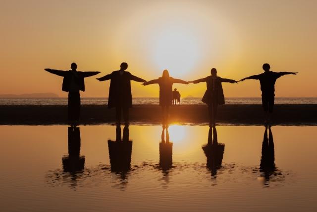 海辺で5人の男女が手を広げてポーズを取っているシルエットの画像