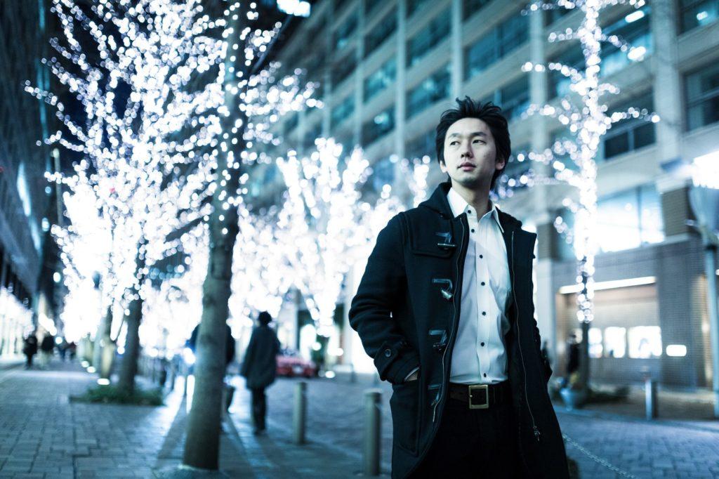 都心をロングコートで歩いている男性の画像