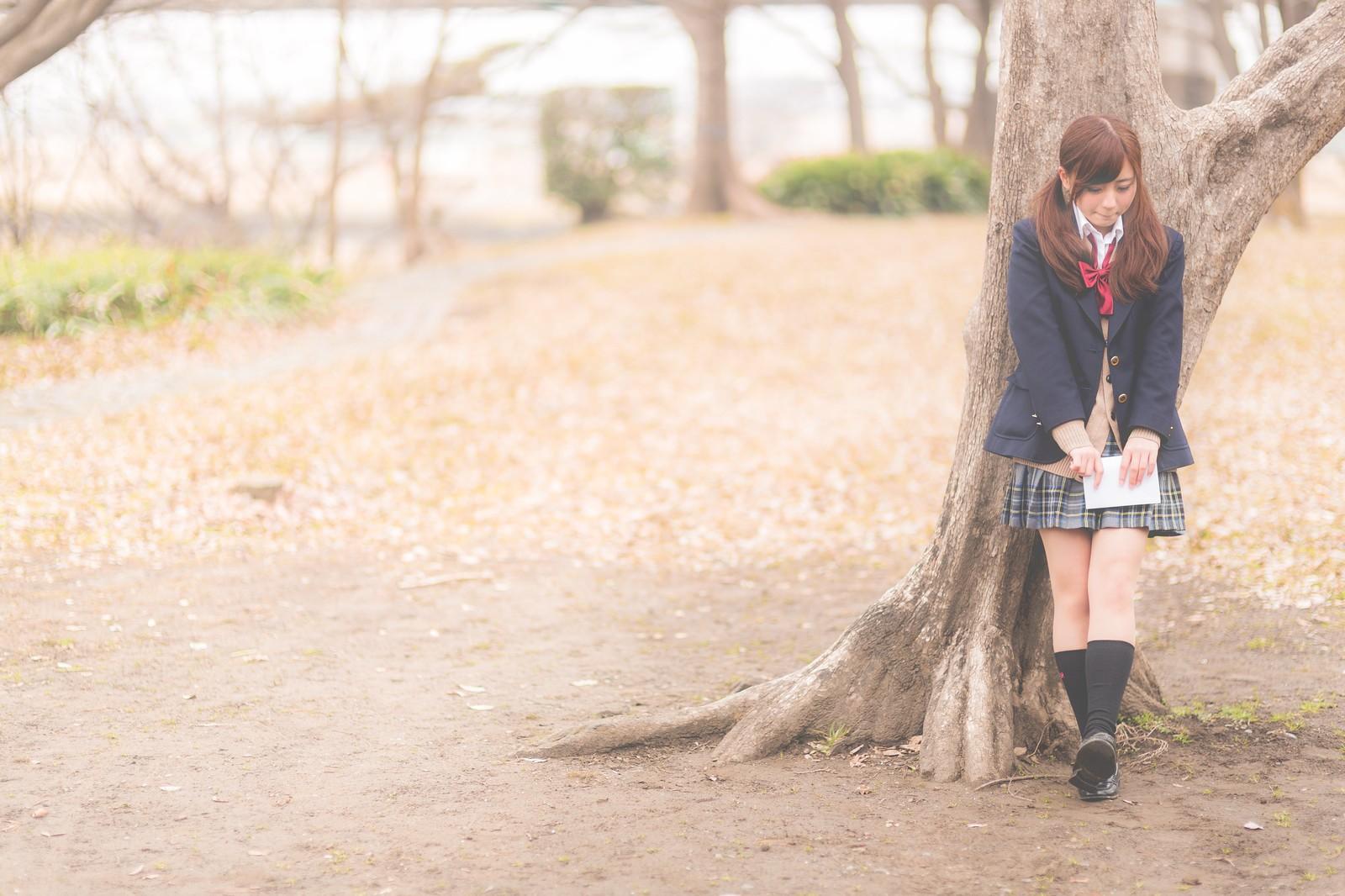 将来が不安と木にもたれかかっている女子高生の画像