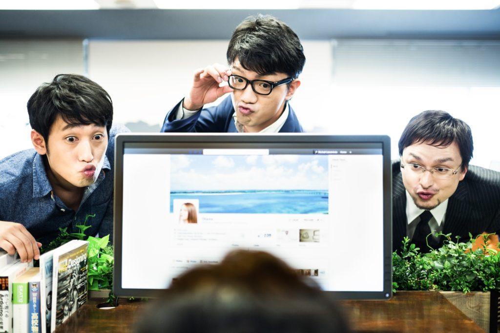 将来が不安な方に事前に準備が出来る方法をパソコンで教えている3人の会社員の画像