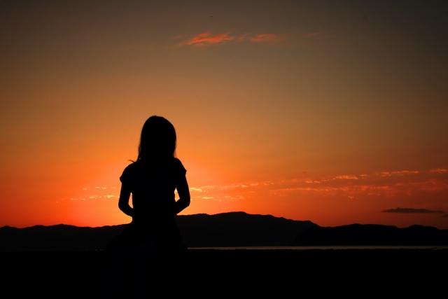 夕焼けを見ている女性の後ろ姿の画像