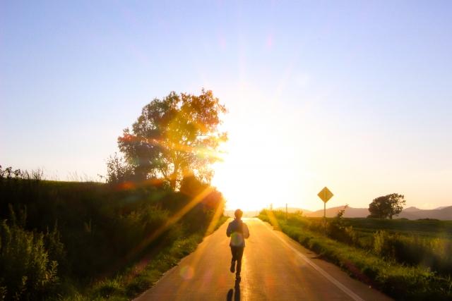 夕焼けの道をランニングしている人の画像