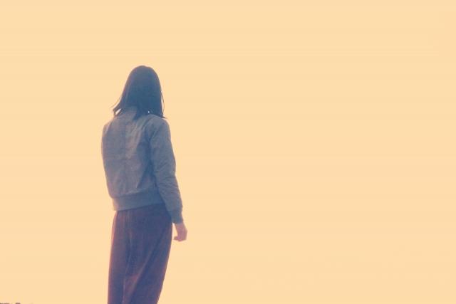 心から笑えなくなった女性が海を眺めている画像