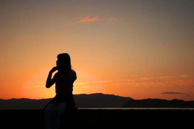 夕焼けの中、一人で座っている女性の画像