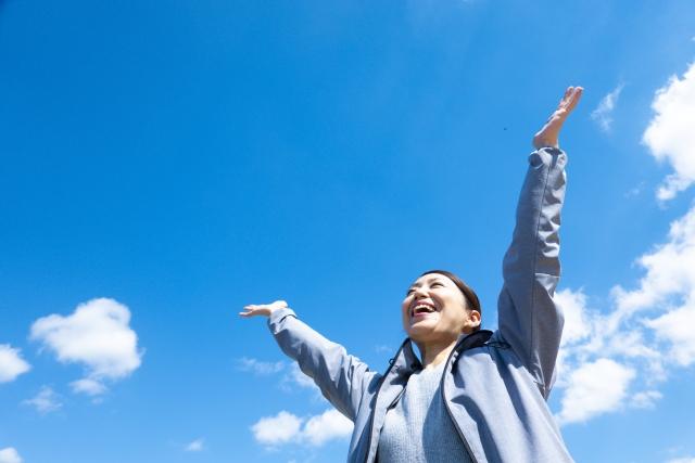 快晴の空に向かって大きく両手を広げている女性の画像