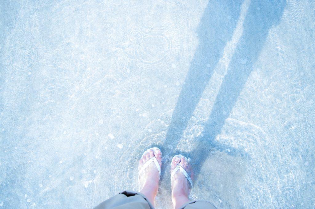 浅瀬にビーチサンダルを履いている女性の足元の画像