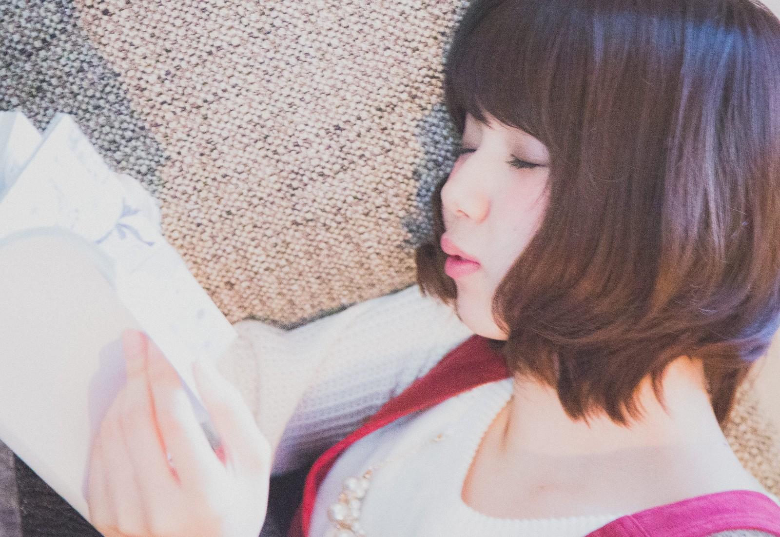 気軽に生きる方法が書かれている本を読んで寝てしまった女性の画像
