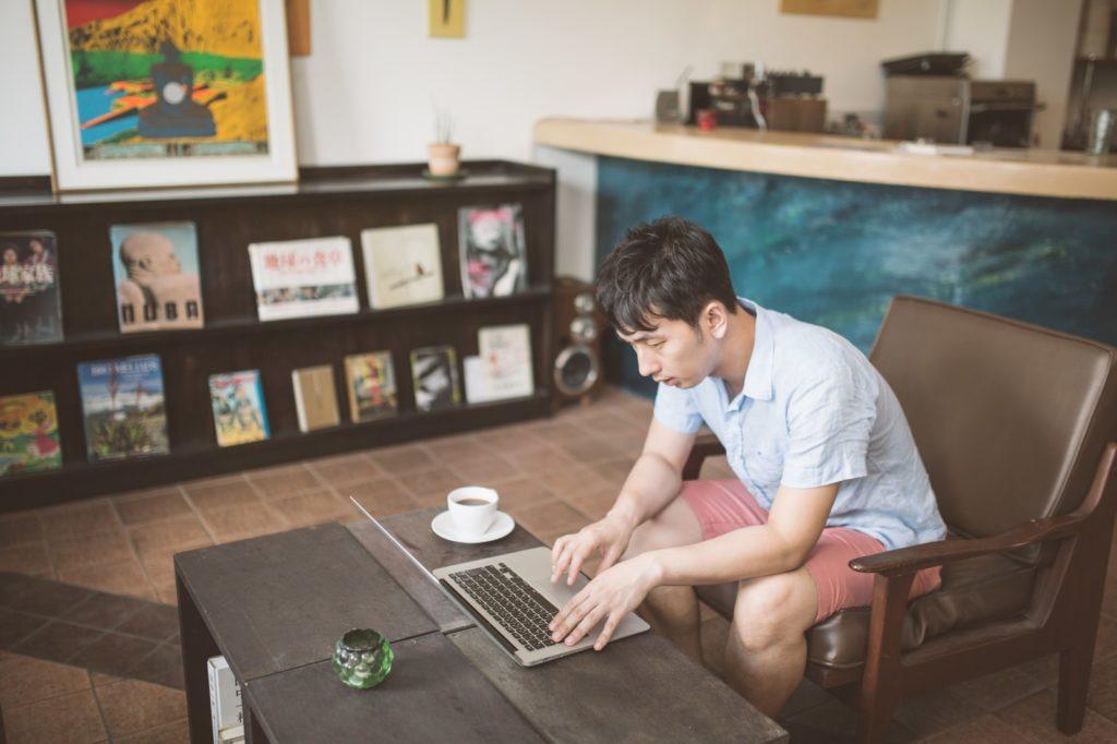 自分で考える力を手に入れる20のコツを資料にまとめているパソコン男性の画像