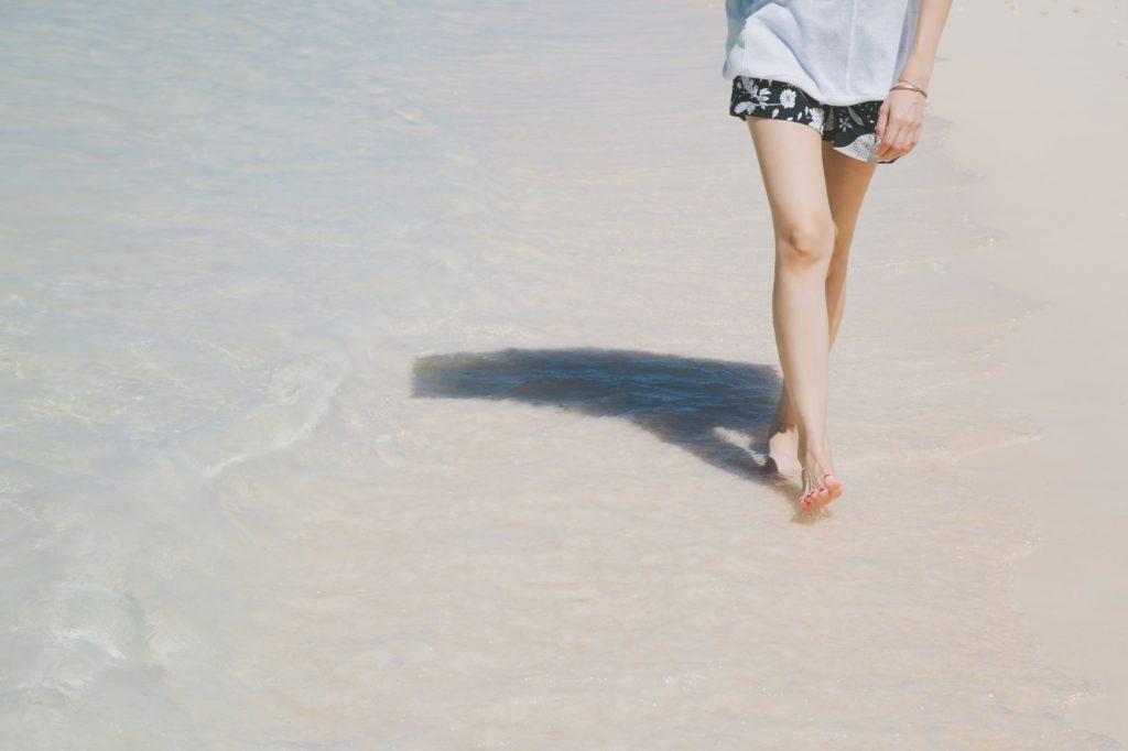 海辺を歩いている女性の脚元の画像