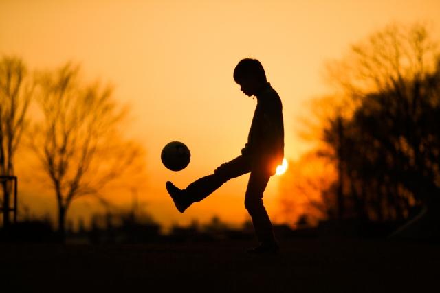 人生どうでもいいと落ち込んでいる夕焼けの中サッカーボールをしている子供の画像