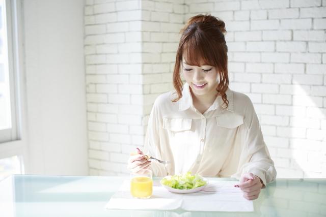 置き換えダイエットとしてサラダを食べている女性の画像