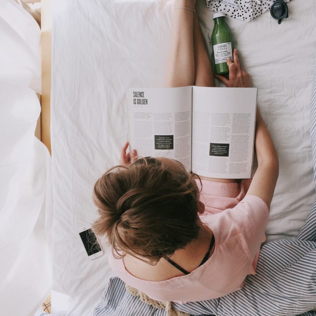 ベッドで本を読んでいる女性を頭上から撮った画像