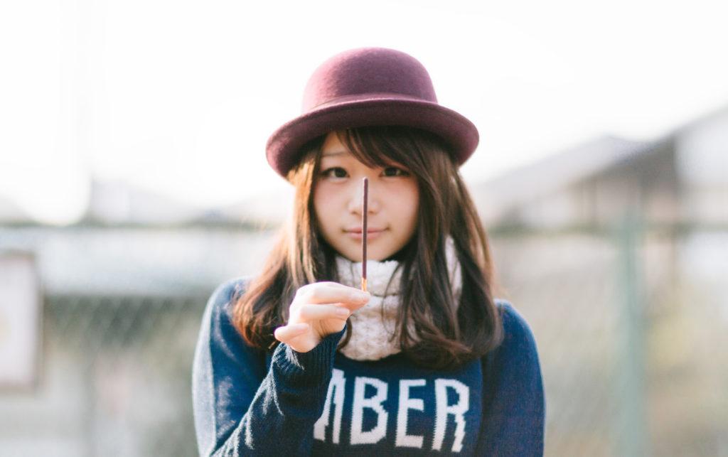 ポッキーを片手に持っている女性の画像