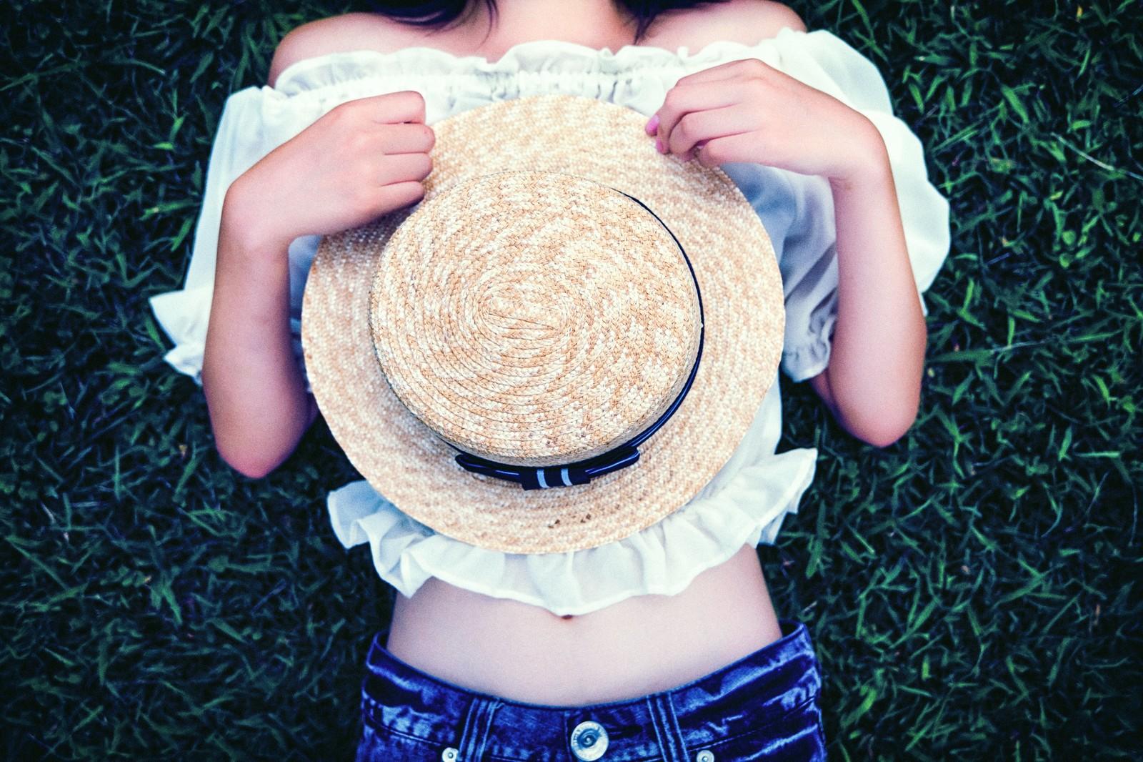 置き換えダイエットを決意したお腹を出した服を着ている帽子を持った女性の画像