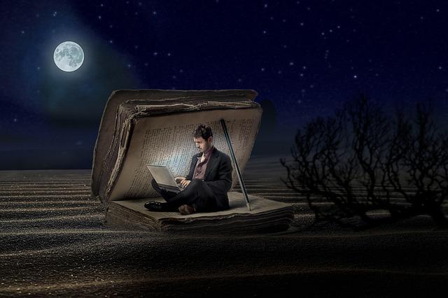 月の出る夜の明かりに照らされながらパソコンをしている男性の画像