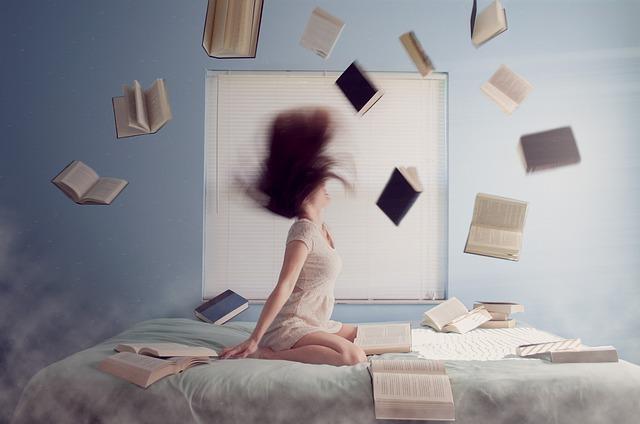 人生どん底に落ちてベッドの上で本を投げ飛ばしている女性の画像