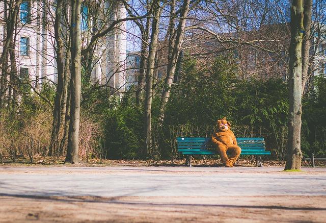 公園のベンチで一人寂しく熊の着ぐるみを着た人が座っている画像