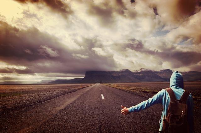 長い広大な一本の道路に両手を広げている旅人の画像