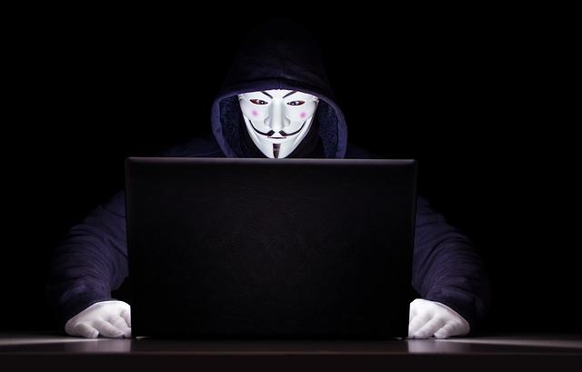 暗い中、パソコンを開きブログの裏技を調べている白い仮面の男性の画像