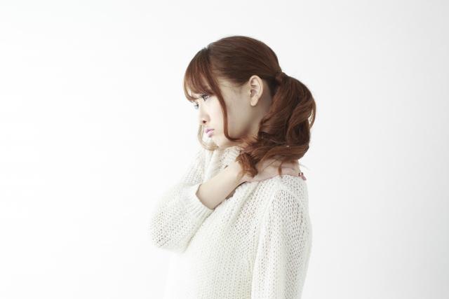 肩こりを感じて肩を触れている女性の画像