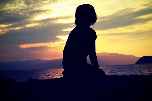 夕焼けを眺めている女性のシルエットの画像