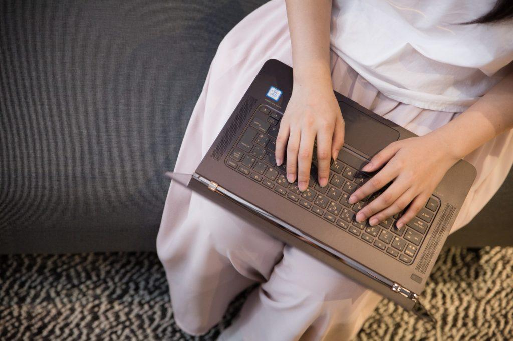 パソコンでブログをしている女性の画像
