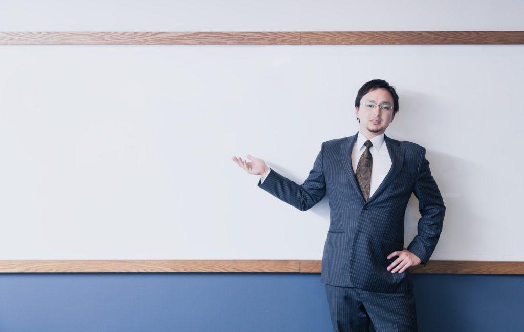 フリーランス貧乏の特徴をホワイトボードで説明しているスーツ姿の男性の画像