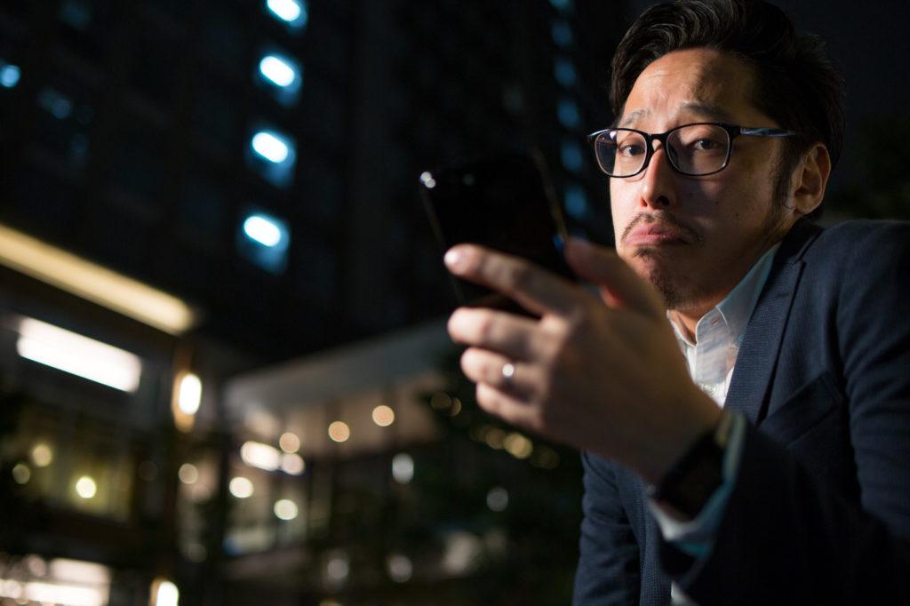 夜、外でスマホを眺めている男性の画像