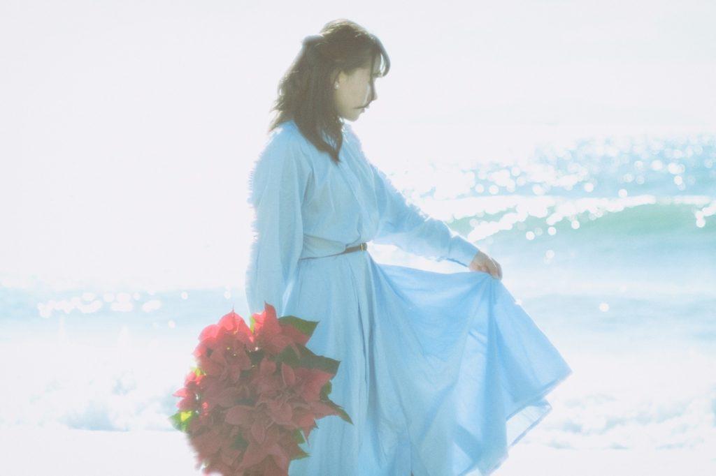 海沿いに白いワンピースを着て赤い花束を持っている女性の画像