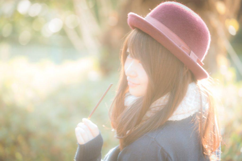 赤い帽子を被ってポッキーを持っている美女の横顔の画像