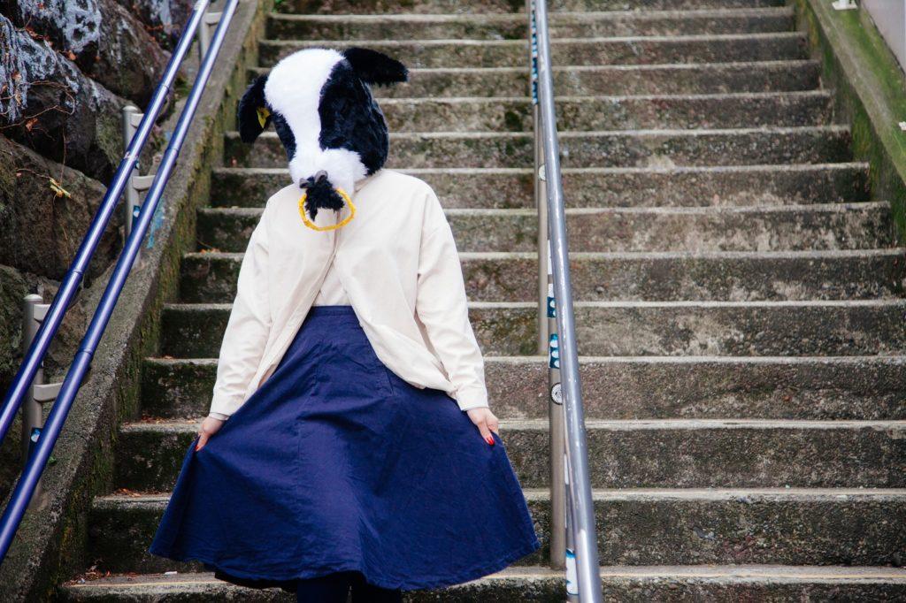 階段で占いに依存してしまい人生がわからなくなって落ち込んでいる牛の被り物をしている女性の画像