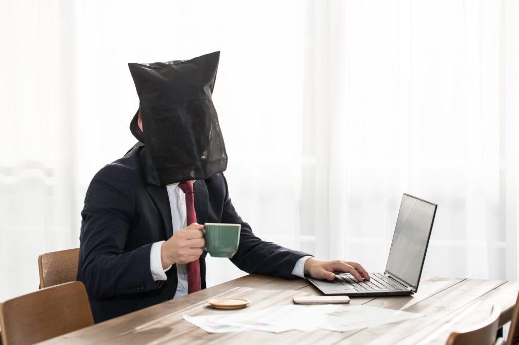 黒い布を被ったスーツ姿の男性がコーヒーを飲みながらパソコンをしている画像