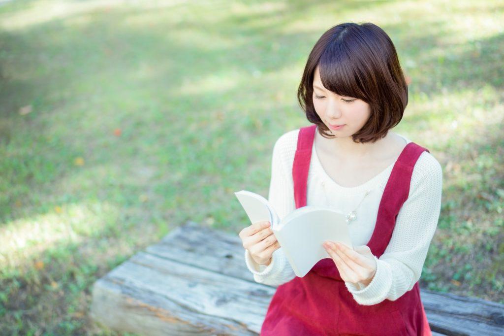 占いを信じる人女性がスピリチュアルな本を読んでいる画像