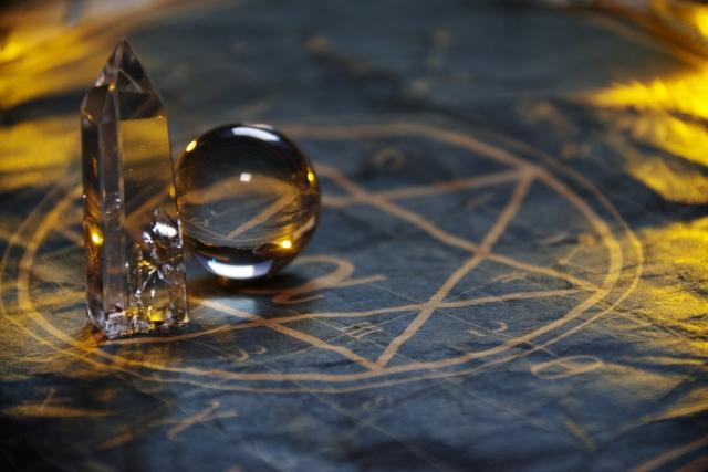 占いで使う水晶と六芒星の書かれたテーブルの画像