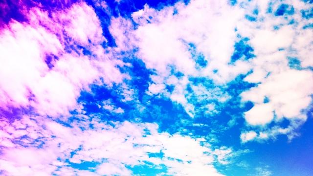 虹色に光る青空と雲の画像