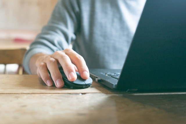 占いを信じない人の特徴をパソコンで調べている男性の画像