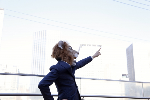 空に向かって指をさしているライオンの被り物をしたスーツ姿の男性の画像