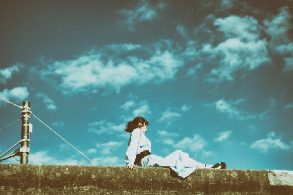 女性が青空の下で座っている画像