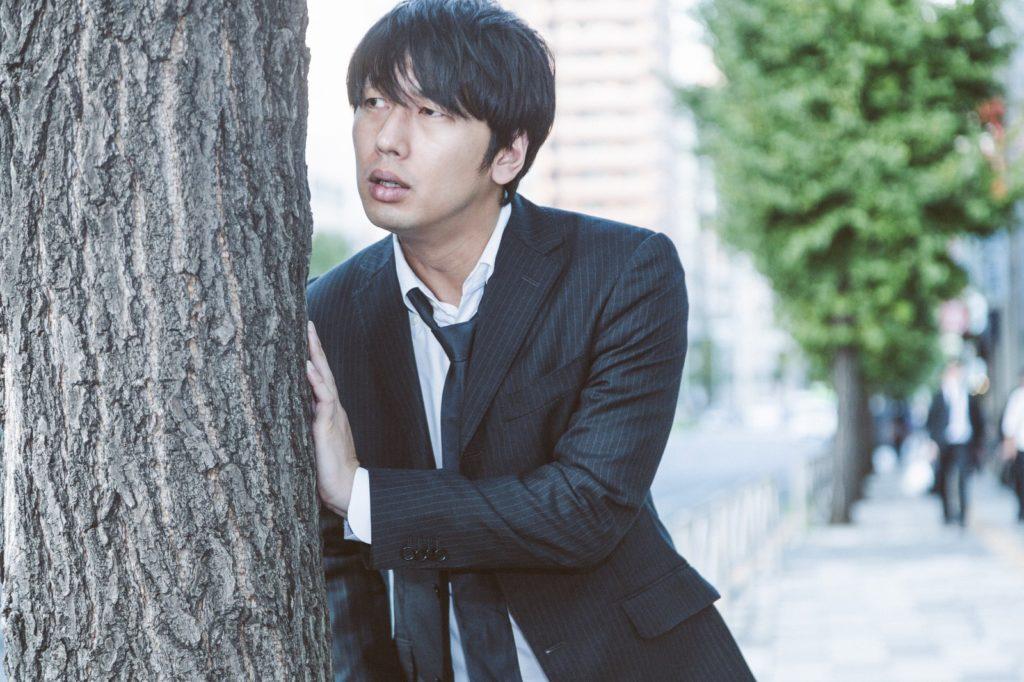 木に隠れているスーツ姿の男性の画像