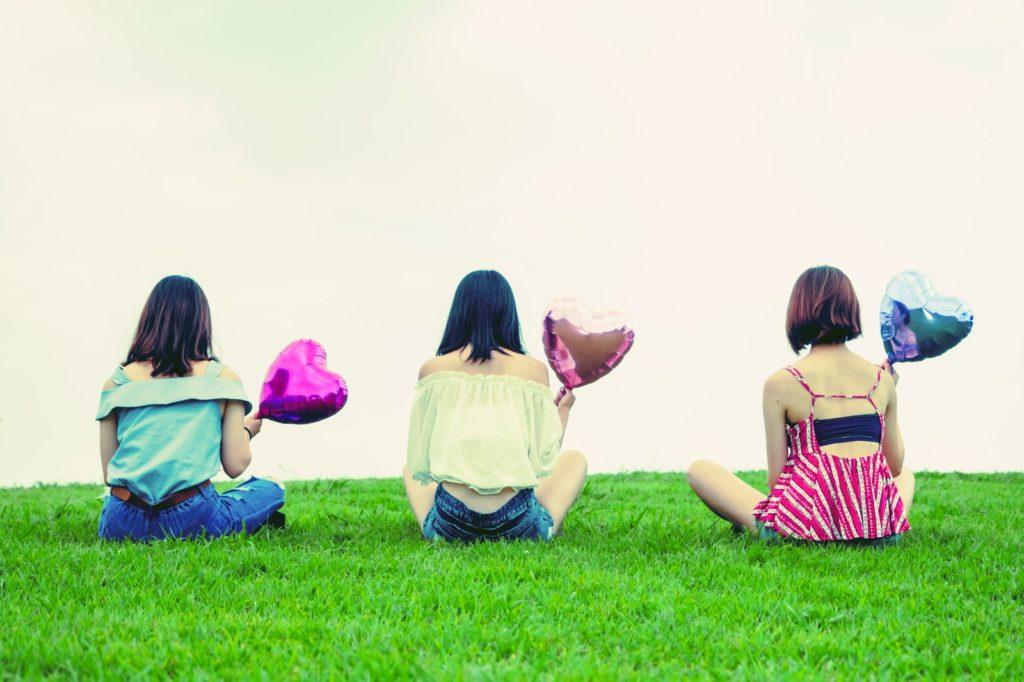 風船を持って芝生に座っている3人の女性の後ろ姿の画像